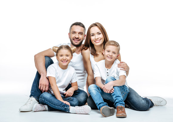 Smiling family of four in white t-shirts, happy with health insurance in Bristol, VA